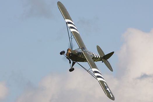 The Piper J-3 Cub G-AKAZ painted to represent a Piper L-4 observation aircraft with invasion stripes performing at the VE-Day Airshow, Duxford.