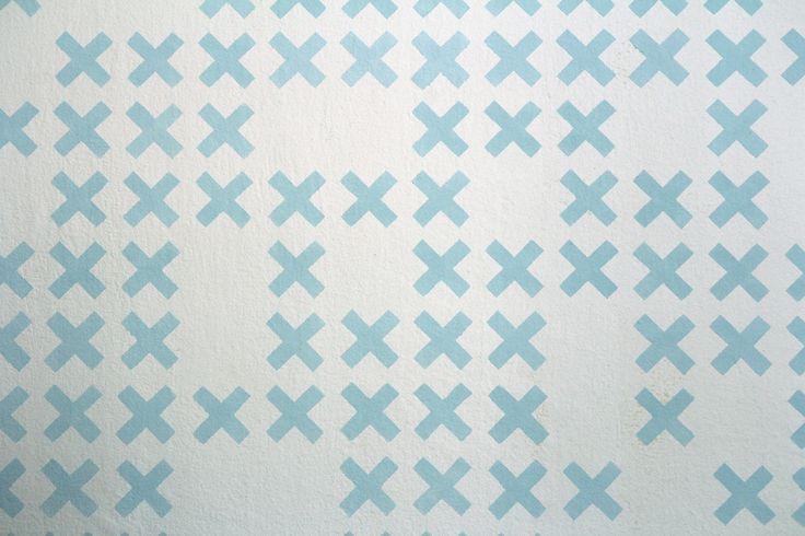 Šablonová malba, vzor Křížky. Jednobarevná šablona na bílém podkladu. / Pattern painting on the wall called Small crosses.