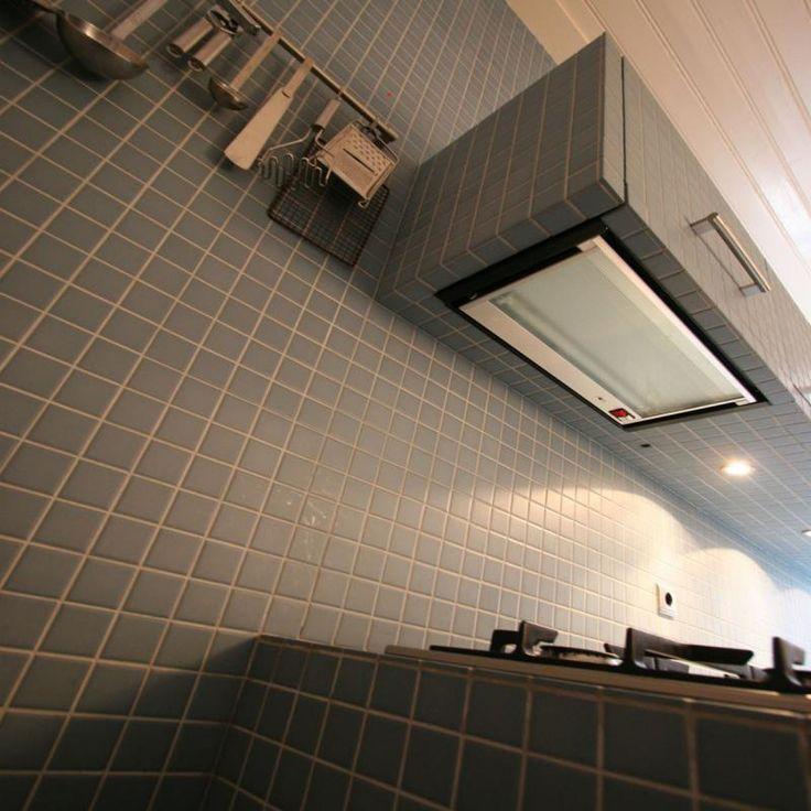 Betegelde bovenkastjes in volledig betegelde keuken. Ik heb een 'standaard' keuken zo aangepast dat de maatvoering overeen kwam met de maat van een veelvoud van de tegeltjes. Een zeer geslaagd experiment!