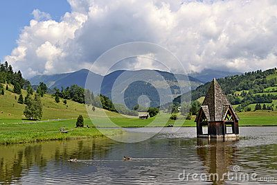 Austrian Alps, a church inside a pond near Rottenmann village with mountains in background