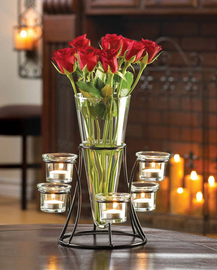Place fresh flowers in the vase and watch as their beauty intensifies with the help of glowing candlelight. The black metal frame of this fantastic accent piece holds a tapered glass vase surrounded by six glass candle cups waiting to be filled, creating a dramatic display.