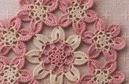 Flores cor-de-rosa do crochet.  Um trabalho bonito com em padrões do fio