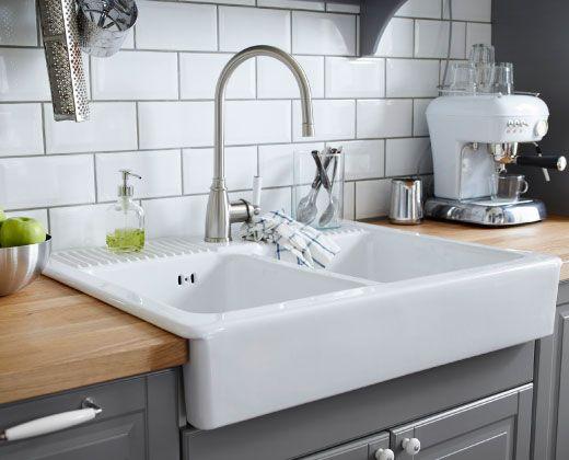 Fregadero doble de porcelana instalado en encimera maciza y rodeado de electrodomésticos de cocina portátiles