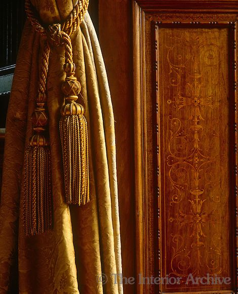 A Gold Coloured Curtain Tassel On A Damask Curtain Next To An Inlaid Door  Panel