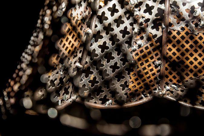 Laurence Seventer maakt in haar Den Haags atelier (NL) buitenaards mooie moderne lusters en objecten uit recupmaterialen zoals fiets- en motokettingen, geperforeerde metalen platen, auto-onderdelen en andere afgedankte rommel die ze vindt op haar strooptochten langs metaalfabrieken, fietsenmakers en schroothandelaars.  Hanglamp van recup geperforeerde staalplaat