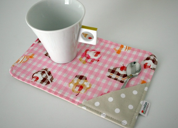 """Mug rug é um """"tapetinho de caneca"""". Um mini jogo americano para ser usado na hora do lanche ou do chazinho.  Feito em tecido de algodão japonês e nacional e forrado com manta acrílica. Possui um bolsinho lateral para colherzinha ou saquinho de chá.  Medidas aproximadas: - Largura: 22,5 cm - Altura: 14,5 cm  Obs: a caneca e a colher NÂO acompanham o produto. O preço refere-se a 1 unidade. R$22,00"""