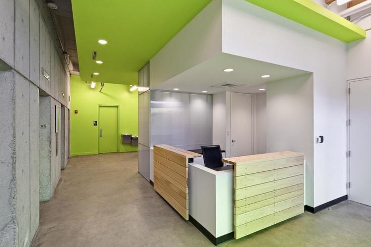 green ceiling + accent wall draws eye beyond reception desk.