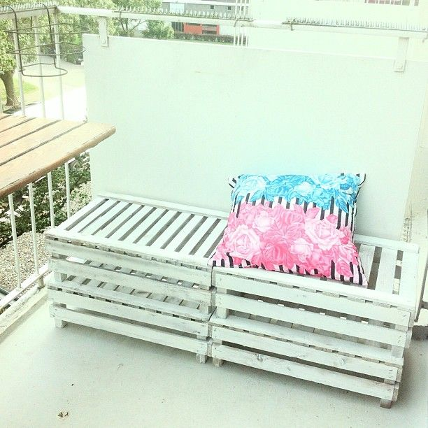 Another way to use crates as balcony seating.  By painting them the same color as the balcony, they look built in.