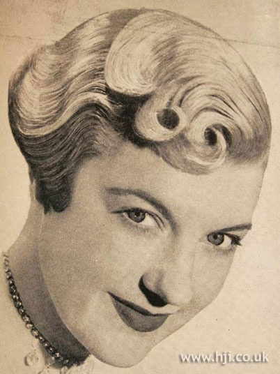 1950 short curls hairstyle    Short blonde hair was brushed back into a duck tail and the front section was brushed over onto the face with soft curls through the ends     Hairstyle by: Henry da Costa