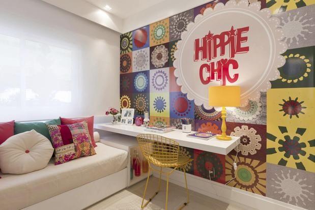 Quarto de menina com parede revestida de vinil com estampa tipo patchwork + cama box com colcha clara e almofadas coloridas + mesa de estudo de laca branca + cadeira Bertóia amarela.