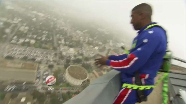 Basketball star scores basket from dizzying height - Harlem Globetrotter star climbs on top of San Antonio tower to shoot a basketball and score from a height of 178 meters