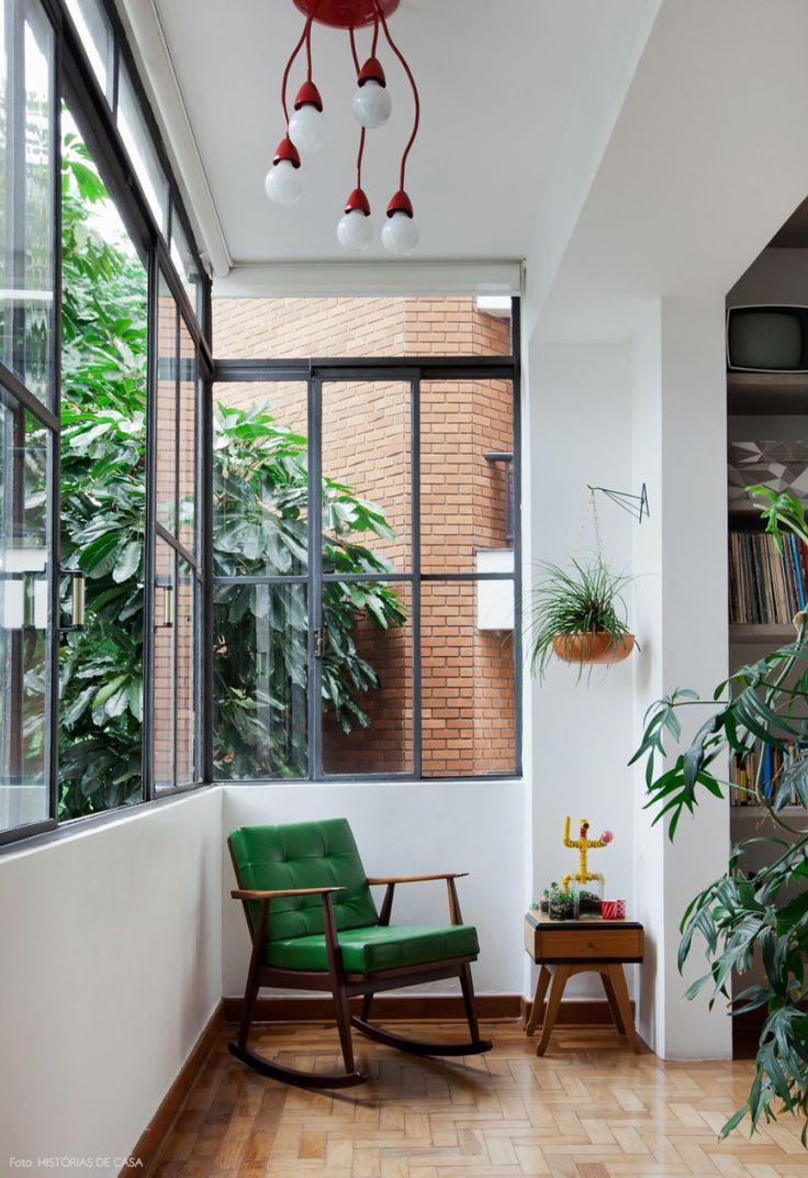 Cantinho de leitura bem iluminado com poltrona revestida de couro verde, criado mudo vintage e plantas.