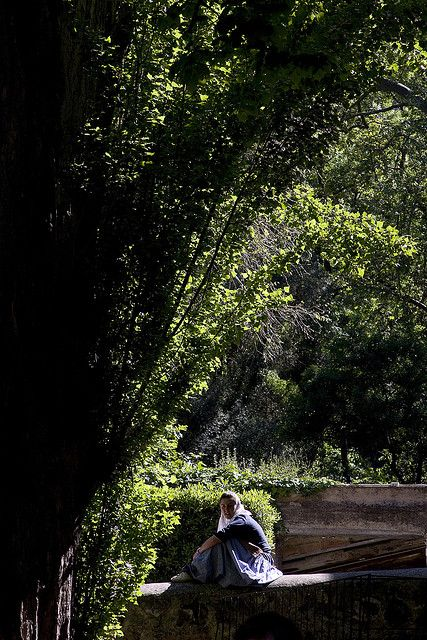 A girl in traditional dress takes a break in the sunshine before a dance performance at La Granja in Mallorca.