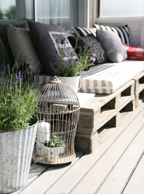 Inexpensive outdoor seating--use old pallets along with cushions and pillows to create a rustic bench!