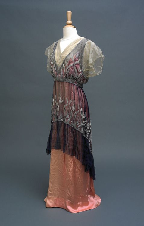 Evening Dress   c.1914 Mrs Pialat Delanoue, Paris Accession No: KINCM:1976.49e Brief Description: An evening dress of pink silk with blue chiffon over-tunic reaching just below knee level, decorated with sparkling beadware. Fastens at back with hook and eyes.