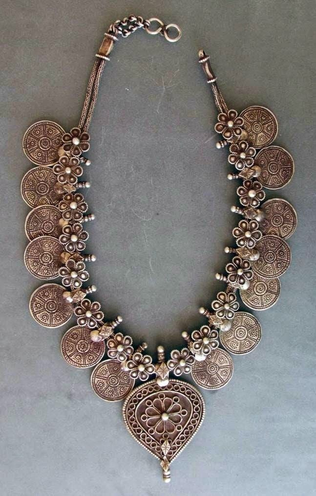 """Silver necklace (""""kanthiolo hullar"""") from the early 20th century, from Gujarat. It is 14 round pendants & a central pendant strung on knitted wire, with a back hook. In between the round pendants are 16 flower shaped smaller spacers."""