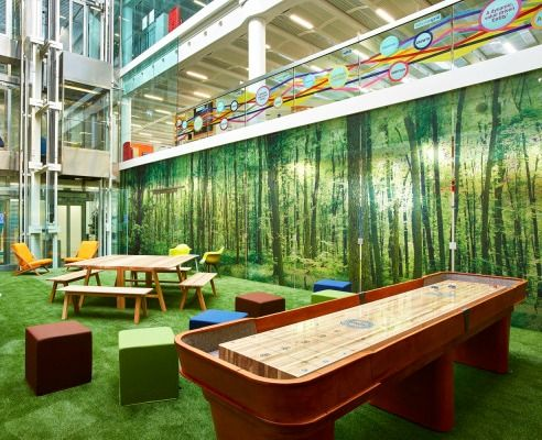 Is this a breakout area at Google? No this fun green space is actually a breakout space at National Grid's Solihull office. We transformed the ground floor of the atrium area of this workplace into an indoor woodland with printed woodland curtain, faux grass and a picnic table to relax and enjoy the scenery.