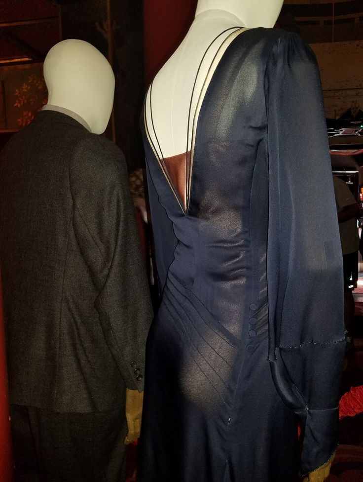 chiffon-like fabric, semi transparent, decorative stitching (lines across butt and on front, with buttons where stitches end), odd seam middle forearm that seems to be embellished, hidden zipper on the right side seam