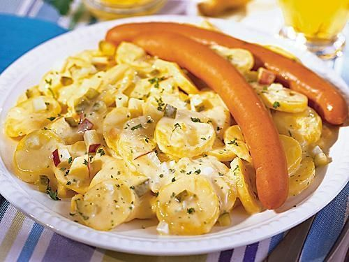 German potato salad (Kartoffelsalat) with eggs, pickles, and Frankfurter sausages, one of the best foods for grill-outs and picnics.