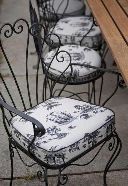 French - Wrought iron chairs with upholstered cushions at an outdoor seating area. I love the curly back!