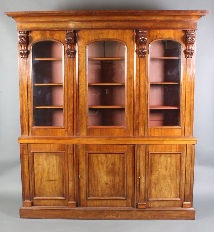 """Lot 876, A Victorian mahogany triple bookcase on cabinet the upper section with moulded cornice, fitted adjustable shelves enclosed by arched panelled doors with vitruvian scrolls to the base, the base fitted triple cupboards enclosed by panelled doors and raised on a platform base 83""""h x 77 1/2""""w x 14"""" (made up), est £150-200"""