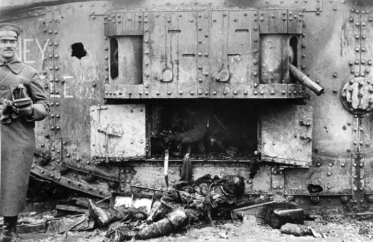 German soldier holds a camera, standing in front of a destroyed British Mark IV (female) tank and the burned remains of its crew in 1917. (D...