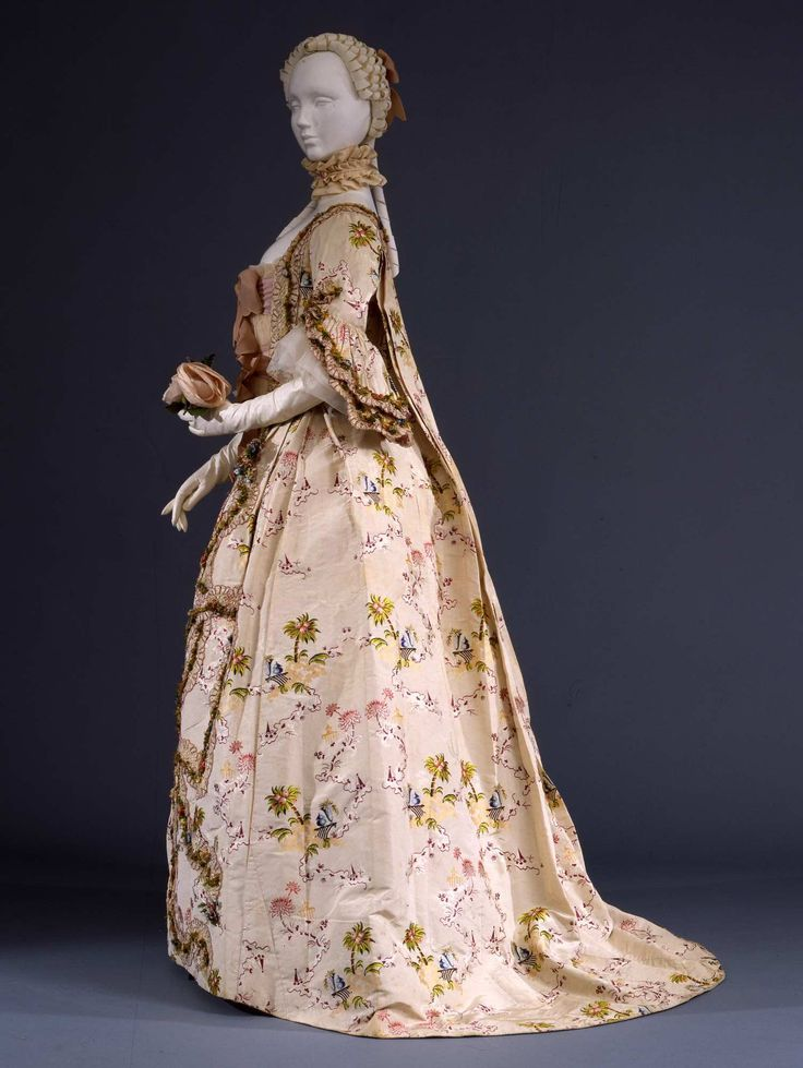 "Side view, robe à la francaise, propably France, ca. 1760-1765. Ivory silk ""gros de Tours"" embroidered with a design of floral motifs and exotic landscapes in polychrome silk, trimmed with flye fringe."