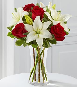 Rich red roses pop against a backdrop of bright white Asiatic Lilies