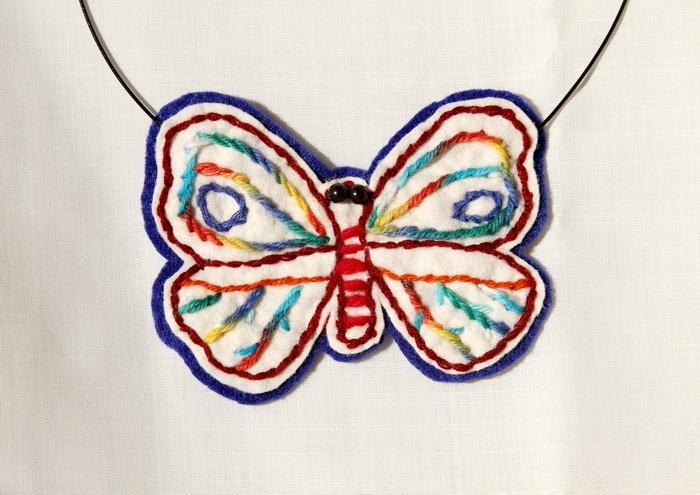 Colier cu fluture brodat cu ata multicolora, realizat din fetru albastru si alb, cu margele negre de mena Breslo