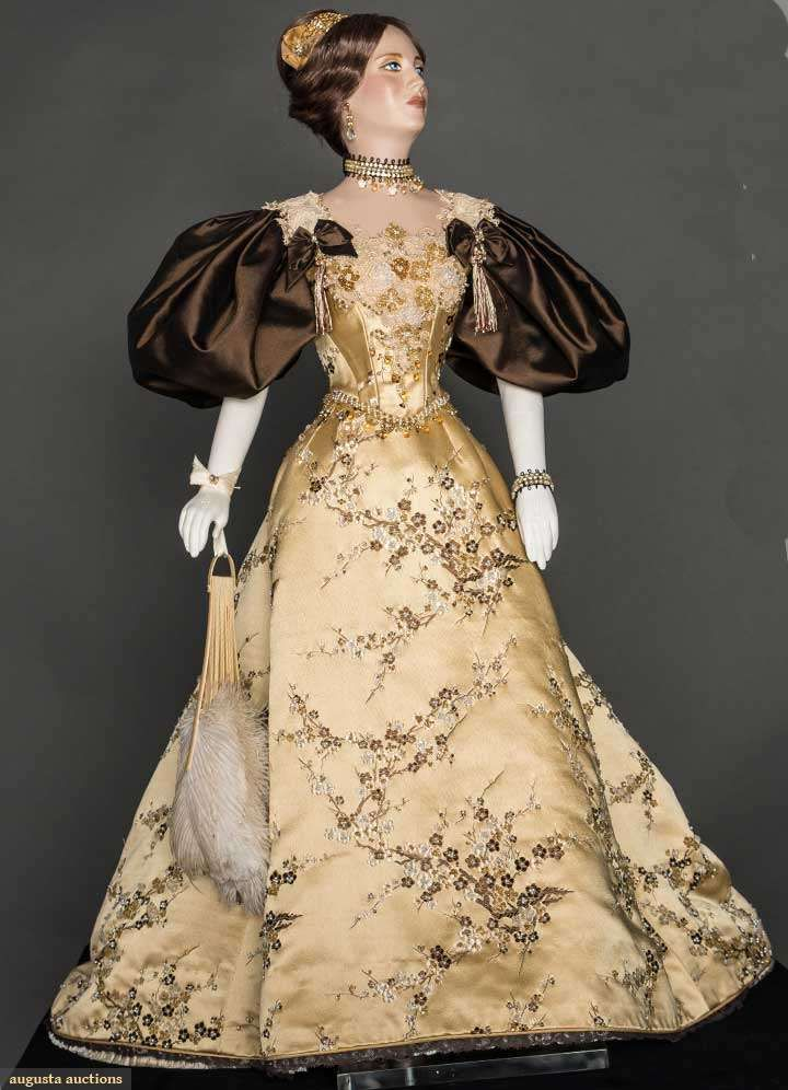 "29"" figure, period accurate 1893 ball gown created & hand sewn by fashion designer John Burbidge: gold silk satin brocaded w/ plum blossoms & hand applied pearls & beads, pearl & bead jewelry & hair piece, includes hand fan, undergarments & shoes, all excellent. This is one of 75 ""ladies"" each costumed in a 1860 through 1914 unique ensemble, as seen in the book ""Les Petites Dames de Mode"" & numerous museum presentations throughout the U.S."