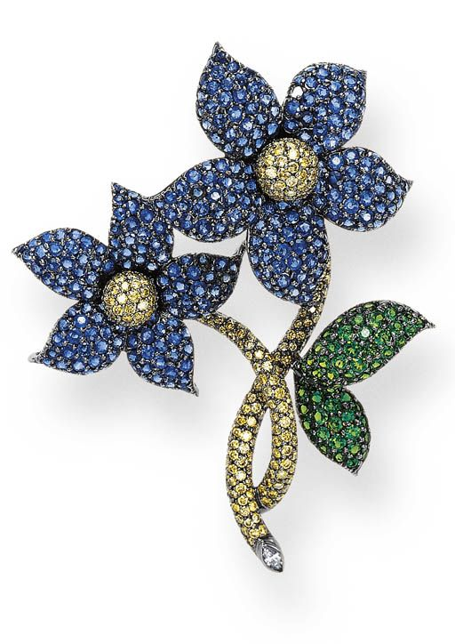 A SAPPHIRE, YELLOW DIAMOND AND TSAVORITE GARNET BROOCH. Designed as two entwined flowers, each with pavé-set yellow diamond sphere pistils, extending pavé-set sapphire petals, with pavé-set yellow diamond stems, one with a marquise-cut diamond terminal, enhanced by tsavorite garnet leaves, mounted in oxidized white gold.
