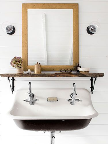 Anthropologie's iron brackets turn a slab of repurposed wood into a shelf in this master bath. The sink is Kohler.