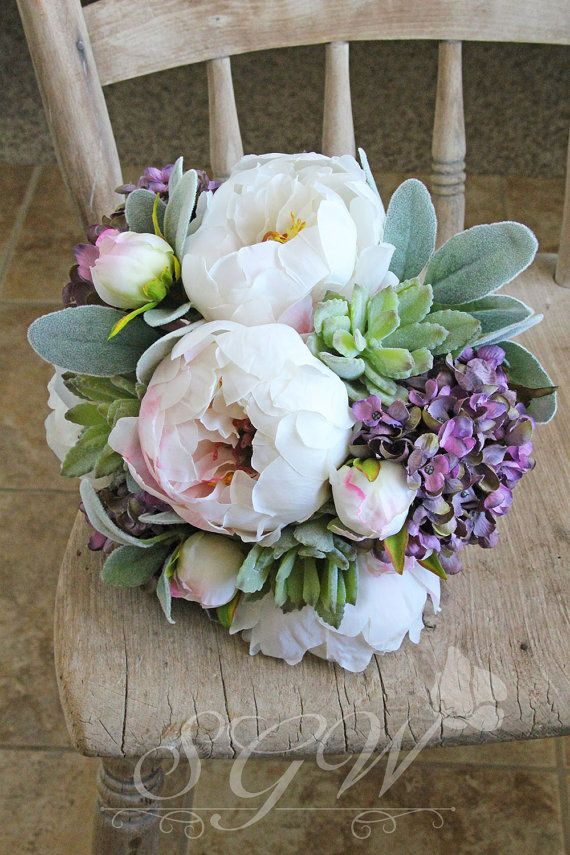 This gorgeous, realistic succulent bouquet features white peonies, lavender hydrangea, soft mint green lambs ear and baby agave succulents. The bouquet is wrapped in a bridal white satin ribbon.  The bouquet measures 13 inches tall and 10 inches in diameter.  Southern Girl Weddings bouquets, boutonnieres and corsages are designed with quality silk and real touch flowers. They are made to serve as keepsakes long after your wedding day has passed. They are the perfect alternative for brides…