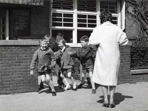 Kleuterscholen : Lachende en drukke kinderen bij het uitgaan van hun school, de   Schoolvereniging Willemspark in Den Haag. Ze worden gadegeslagen door een   vrouw gekleed in witte jas en schoentjes met hoge hakken. Nederland, 1960.