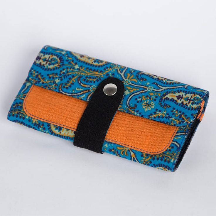 Безупречный женский брендовый кошелек от отечественного бренда Yak Faino, сшитый вручную мастером из трех видов натуральной ткани – джинс, лен и хлопок. Лицевая внешняя сторона имеет модный этнический арабский растительный принт в лазурных тонах , снабжена контрастной черной фронтальной кнопоч