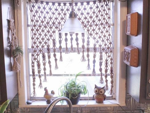 This macrame curtain is woven with 5 ply jute and there is an 18 inch cord on each side for hanging. It is accented with walnut stained wooden beads. This handmade macrame hanging is my version of 70s fiber art. It would work beautifully as a wall hanging or window hanging for your home decor. I love this in a window because it lets the sun in but gives a little privacy. This is custom made. The center length of the hanging is 15 inches and the sides are 32 inches. The wooden beads are 1 1/2…
