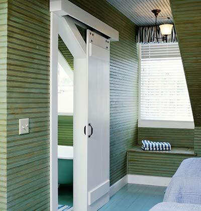 A hanging, sliding door allows easier access between the bath and adjoining guestroom. It takes up much less space than a standard hinged door and adds character and visual interest to the room.  From Southern Living.