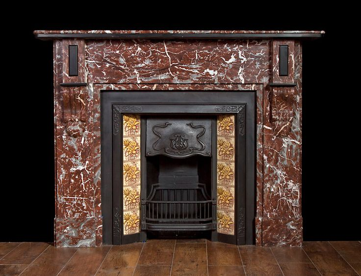 A Rouge Royal marble fireplace with bracket corbels and scallops supporting rectangular end, blocking with black marble details. Pictured with original cast iron Art Nouveau tiled insert.
