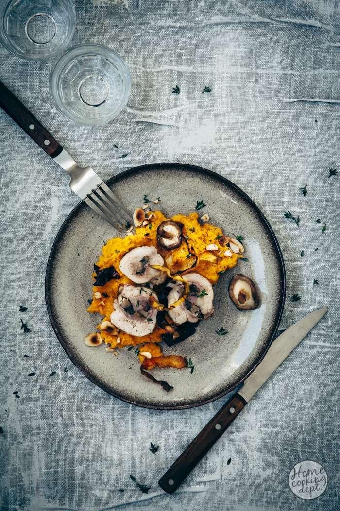 Romige wortelpuree gemaakt van geroosterde pompoen en wortels, met paddestoelen en rauwe ham gevulde kippendijen en wortelchips.