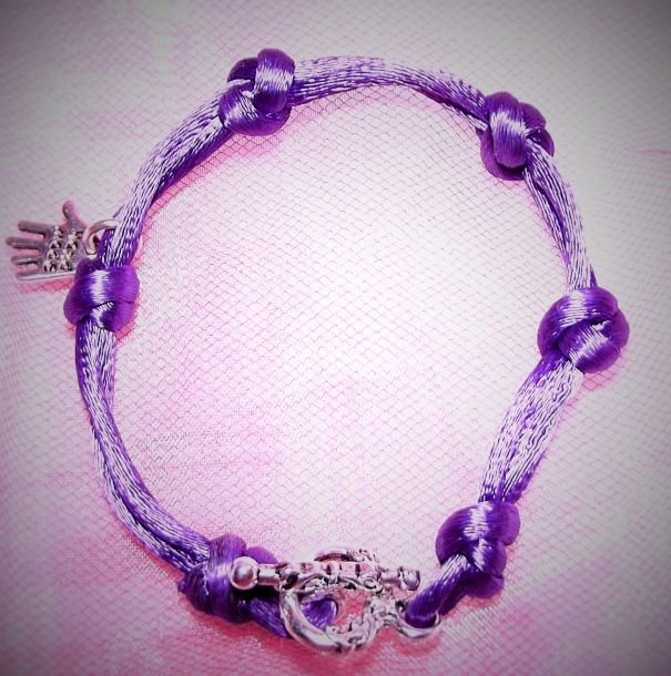 """This satin cord bracelet has been handmade by me in a shiny rich purple colour. It has some super special knots, and a silver plated hand 'hand made' charm. The clasp is lovely and chunky, This bracelet measures 7""""."""