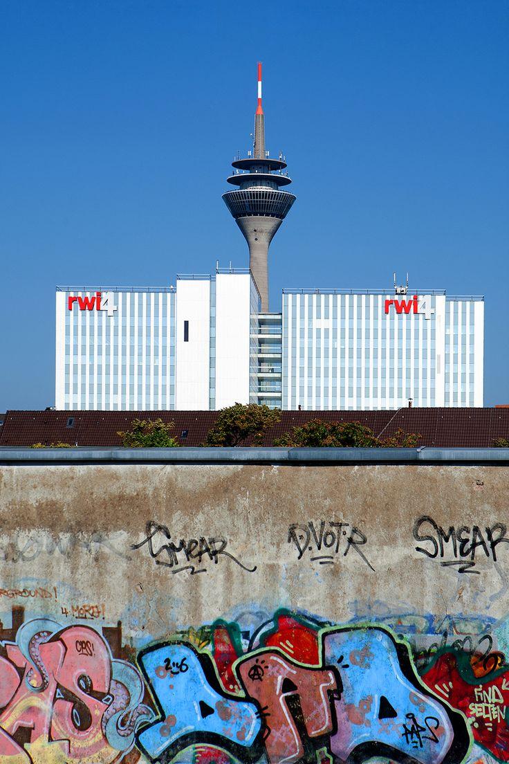 Rheinturm hinter den RWI4 Gebäuden, fotografiert vom Bahnhof Völklinger Straße