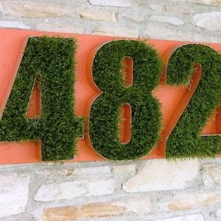 Large grass-filled house numbers on brightly colored board