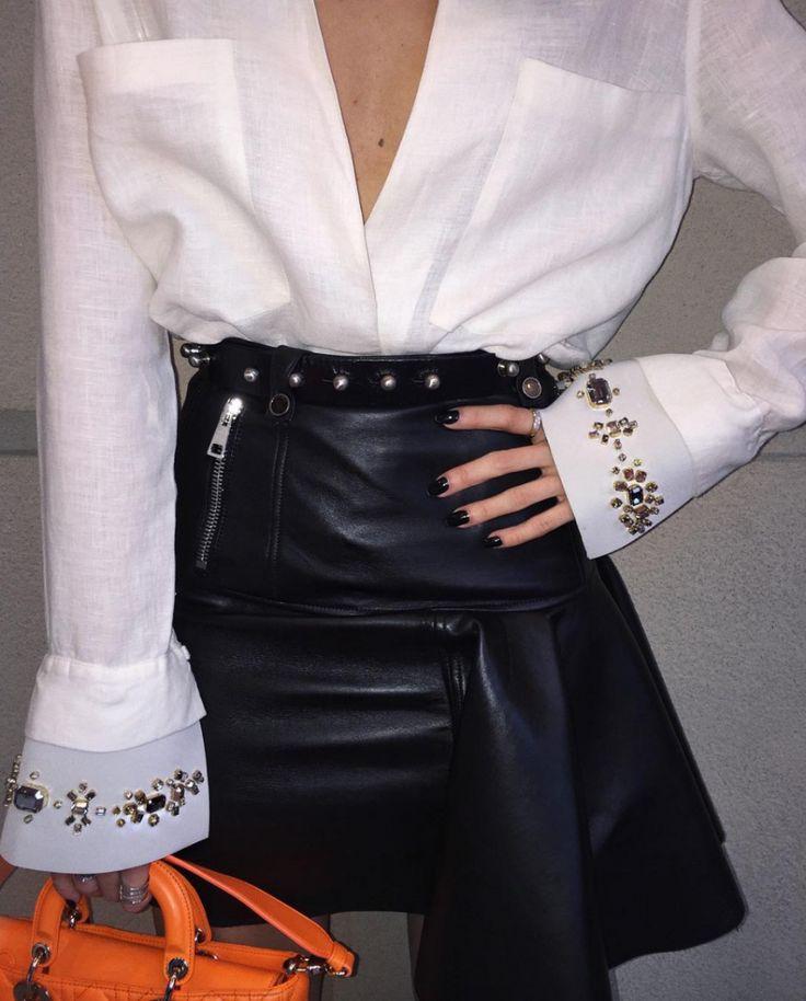 Close do lool da blogueira Camila Coutinho no SPFW. Apostando no preto e branco mas ainda assim saindo do comum, a influencer usou camisa da Osklen com modelagem descontraída e saia de couro rocker em formato A.