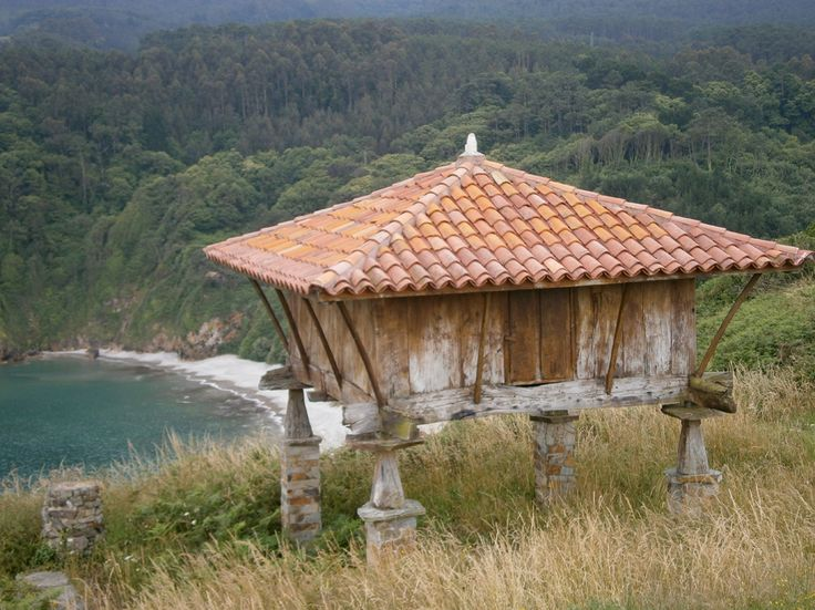 Vista de un hórreo y de una playa en medio de paisaje verde :: Asturias