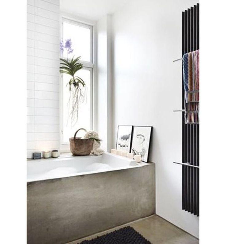 Feminino, este banheiro conta com quadros e velas aos pés da banheira, de cimento queimado