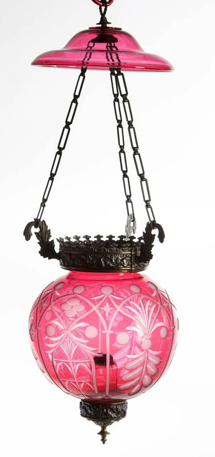 CUT OVERLAY SUSPENSION / HANGING HALL LAMP, ruby to colorless globular-form, intricately detailed pattern with roughened highlights and alternating stylized windows and feather arches, scattered quatrefoils, stars, and swags. Embossed stamped brass foliage frame with matching pattern to top and bottom rim, triple scroll arms support original chains with ceiling mount. Fitted with a ten-panel colorless cylinder-form font, attached to a cast brass support with finial, No. 1 fine-line collar.