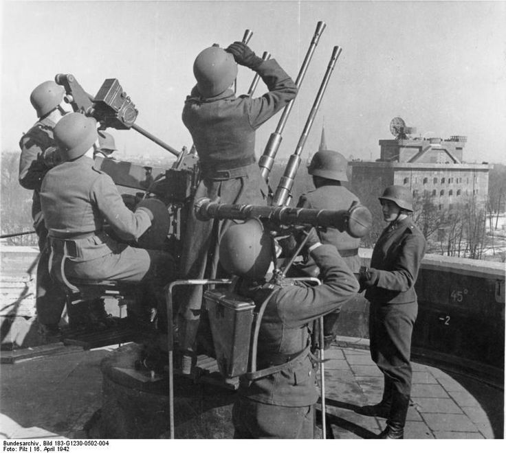 Crew of a Flakvierling 38 anti-aircraft gun atop the Berlin Zoo flak tower, Berlin, Germany, 16 Apr 1942; note range measuring device in foreground and radar station in background