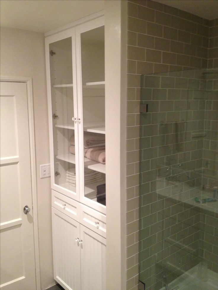 White bathroom linen closet with hamper. Plenty of shelves for storage and hamper on bottom.