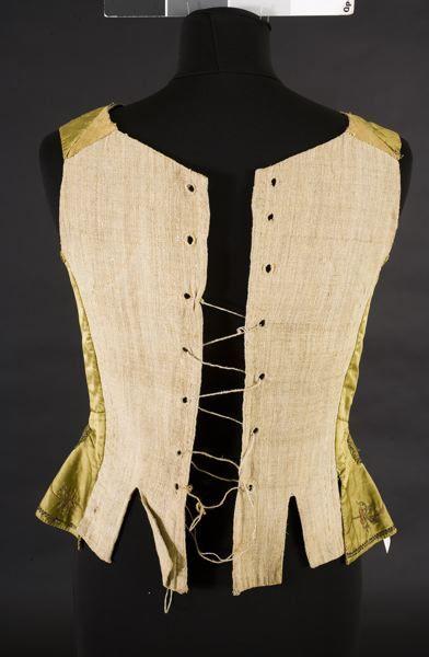 MM 011137 :: väst Damväst av grönt siden med broderier i tambursöm av guld och rött silke och svarta pärlor. Foder av grönt linne. Rygg av grovt, oblekt linne. Knäppes framtill av åtta överklädda träknappar. Snöres i ryggen.