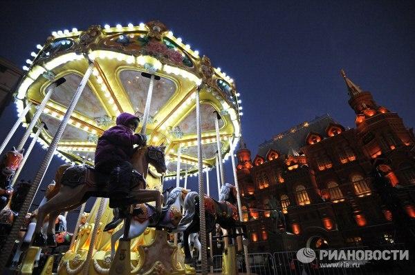 Ребенок катается на карусели на рождественской ярмарке из Страсбурга на Манежной площади в Москве. Фото: Рамиль Ситдиков